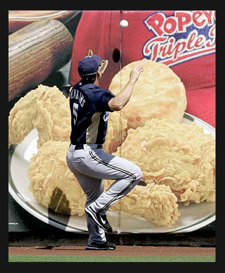 Milwaukee Brewers outfielder Geoff Jenkins battles oversized poultry pieces to try to snag a ball.